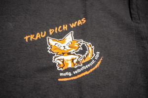 Tshirtdruck: Trau-Dich-Was Logo auf verschiedenfarbigen Tshirts.