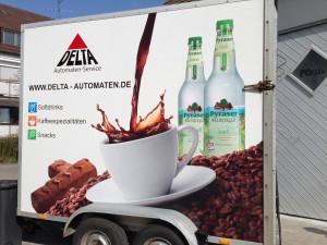 Beklebung eines Anhängers für den Delta Automaten Service mit einem großflächigen Digitaldruck auf Folie von einer Kaffeetasse, Schokoriegeln und Mineralwasser.