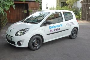 Fahrzeugbeschriftung mehrerer Fahrzeuge für die Diakonie St. Peter in lila und blau, beispielsweiße wie hier auf einem weißen Renault.