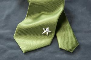 Produktfotografie eines Schmuckstückes in Form eines Sterns, welcher am Ende einer grünen Krawatte befestigt ist.