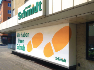 Sichtschutzbeklebung für das Schuhgeschäft Schuh Schmidt in einem Schuhabdruckdesign auf weißem undurchsichtigen Grund und grüner Schrift aus Plotbuchstaben.