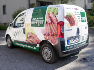 Blick von Hinten auf das Fahrzeug der Metzgerei Meyer im grünen Design mit großflächigen Digitaldrucken.