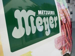 Detailaufnahme des gestochen scharfen digitalen Fotodrucks des Logos der Metzgerei Meyer für eine Fahrzeugbeklebung.