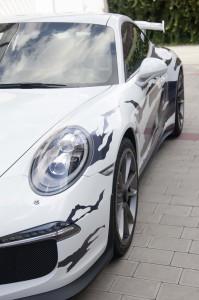 Weißer Porsche GT3 von schräg vorne, halb im Bild zu sehen mit einer schwarz-grauen Streifenbeklebung in Fetzenoptik.