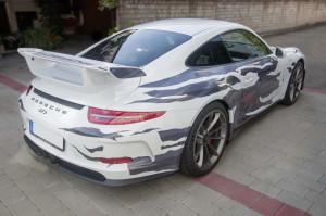 Weißer Porsche GT 3 mit grauer Folienbeklebung in einer zerissenen Optik von schräg hinten.