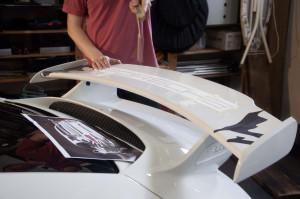 Mann in rotem Shirt bringt eine Heckspoilerbeklebung an einen weißen Porsche GT3 an.