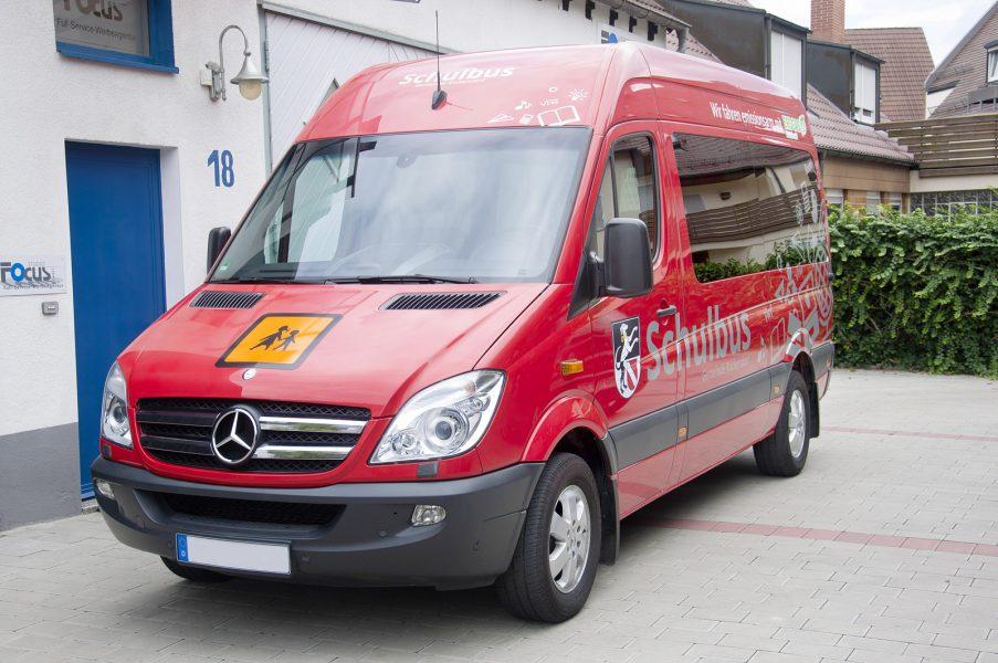 Frontansicht des Schulbusses der Gemeinde Rückersdorf mit sichtbarem Schulbuszeichen, welches als Magnetschild realisiert wurde.