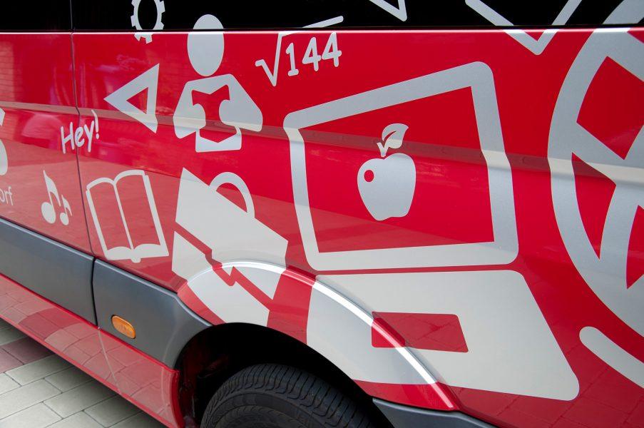 Eine Nahaufnahme des linken hinteren Teils des roten Schulbusses der Gemeinde Rückersdorf der mit verschiedenen grauen Symbolen beklebt wurde.