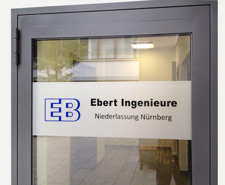 """Blaues Logo der """"Ebert Ingenieure"""" mit schwarzer Folienschrift auf grauer Frostfolie als Sichtschutz/Werbung auf einer Glastür."""