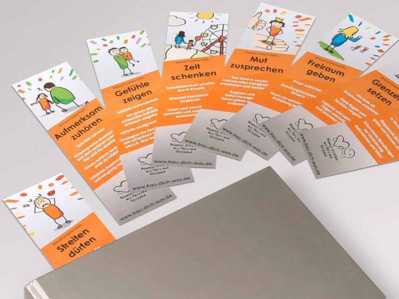 """Aufgefächerte Lesezeichen die für """"Trau-Dich-Was"""" produziert wurden. Orange/Grau mit Illustrationen."""