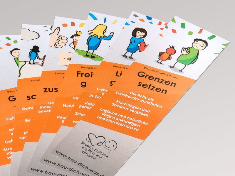 Anordnung verschiedener Trau-Dich-Was Lesezeichen in Orange und Grau - jede mit einer anderen Illustration.