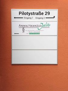 Nahaufnahme der Schildanlage in der Pilotystraße 29. Schwarze Plottbuchstaben auf weißem Alu Dibond Grund.