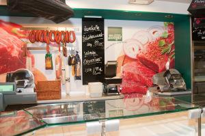 Wandbeklebung mit Fotos von schmackhaften Fleischstücken auf gedruckten Folie in einer Metzgerei.