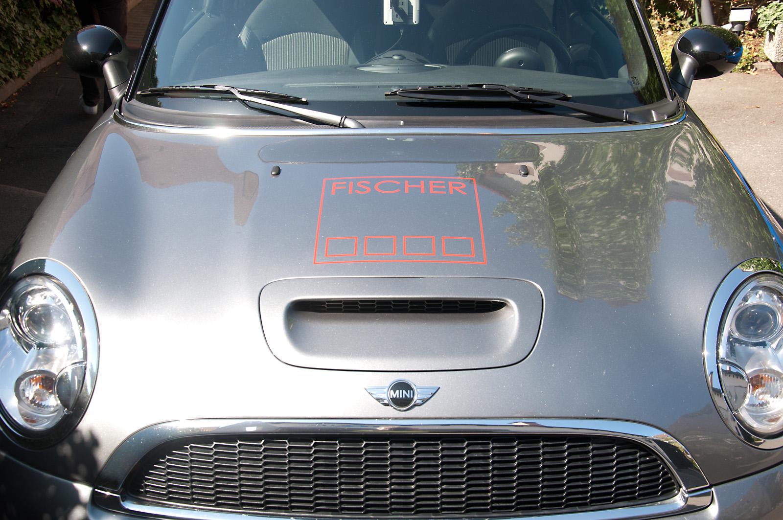 Minimalisitsche Fahrzeugbeklebung für die Fischer Planen und Bauen GmbH - die Konturen des Logos in Rot auf der Kühlerhaube eines Minis.