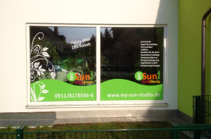 Moderne Schaufenstergestaltung mit weißer und grüner Folie auf der Front des My-Sun-Studios in Nürnberg.