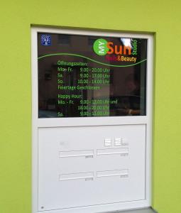 Öffnungszeiten aus grünen Folienbuchstaben im Fenster des My Sun Sonnenstudios in Nürnberg, inklusive Firmenlogo.