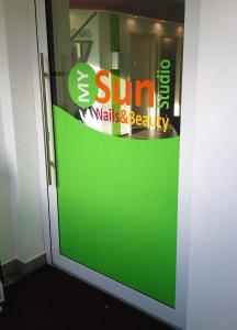 Foliendesign der Eingangstüre des My-Sun-Studios in Nürnberg in den sommerlichen Farben Grün, Gelb, Orange und Rot.