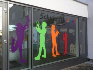 Fensterbeschriftung an der Grundschule in Oberasbach: Mehrere Figurensilhouetten und Schrift in verschiedenen bunten Folie.