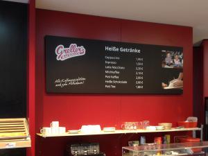 """Sicht auf ein Preisschild in Tafeloptik der Bäckerei """"Greller's Backhaus"""" mit weißer Folienschrift und Fotodrucken."""