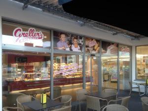 """Komplette Schaufensterbeklebung für den Bäcker """"Greller's Backhaus"""" - Schrift als Folienplott in Magenta auf weißem Untergrund und drei gedruckte Bilder."""