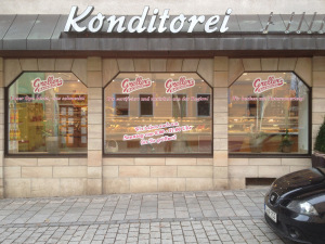 Gestaltete Ladenfront eines Bäckers mit magentafarbener Folienschrift auf einem weißem Hintergrund.