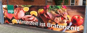 """Winterbanner der Metzgerei Meyer: """"Winterzeit ist Bratenzeit"""" in weißer Schrift vor einem köstlichen Weihnachtsbuffet."""