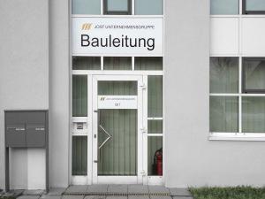 Kennzeichnung der Eingangstür für die Jost Unternehmensgruppe mit schwarzer und goldener Folie auf weißem Grund.