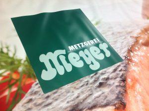 Detailaufnahme eines Banners für die Metzgerei Meyer. Zu sehen ist sein Logo vor einem schmackhaftem Braten.