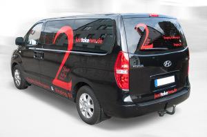 """Werbebeklebung in Rot mit weißen Akzenten auf dem schwarzen Hyundai für die Sänger """"Just take two""""."""