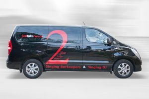 """Rot-weiße Beschriftung des Fahrzeugs für """"Just take two"""" auf schwarzem Grund in der Seitenansicht."""