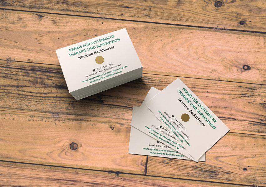 Visitenkarten von Martina Beckhäuser auf einem Holzboden
