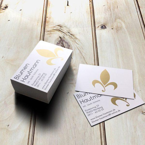 Aufgefächerte Visitenkarten mit simulierten Golddruck auf hellem Holzuntergrund