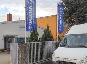 Aufnahme des Firmengeländes von Elektrotechnik Drechsler mit neuen Fahnen und Firmenschild im Hintergrund