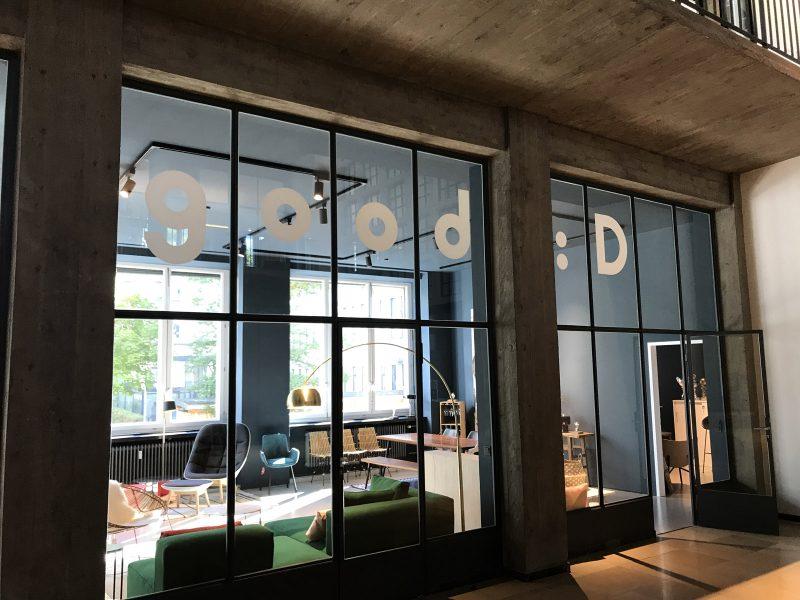 Ausstellungsraum von bsk der von außen fotografiert wurde und eine Schaufensterbeklebung mit dem Shopnamen good:D in großen Lettern hat