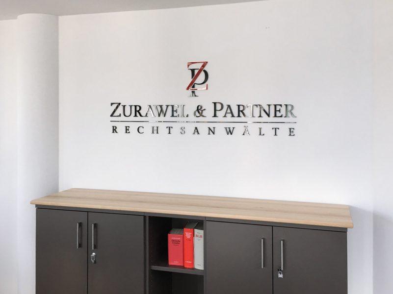 Rechtsanwaltlogo aus Acrylbuchstaben die an einer Wand über einem Büroschrank montiert wurden für Zurawel und Partner
