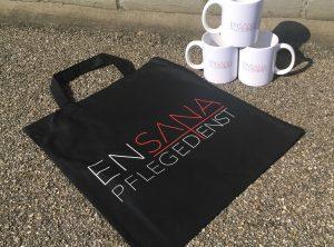 Stofftasche und Tassen mit dem Ensana Pflegedienst bedruckt