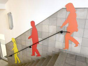 Drei Schattenfiguren in unterschiedlichen Farben an der Wand montiert in einem Treppenhaus bei Siemens