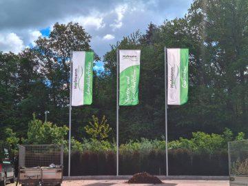 Drei Fahnen mit Masten die auf der Anlage von Garten- und Landschaftsbau Hofmann stehen