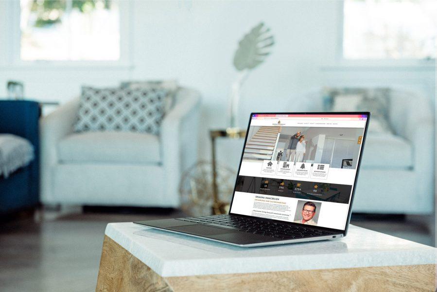 Die Webseite von Skimina Immobilien in einem Laptop an einem gemütlichen Wohnzimmerplatz sichtbar